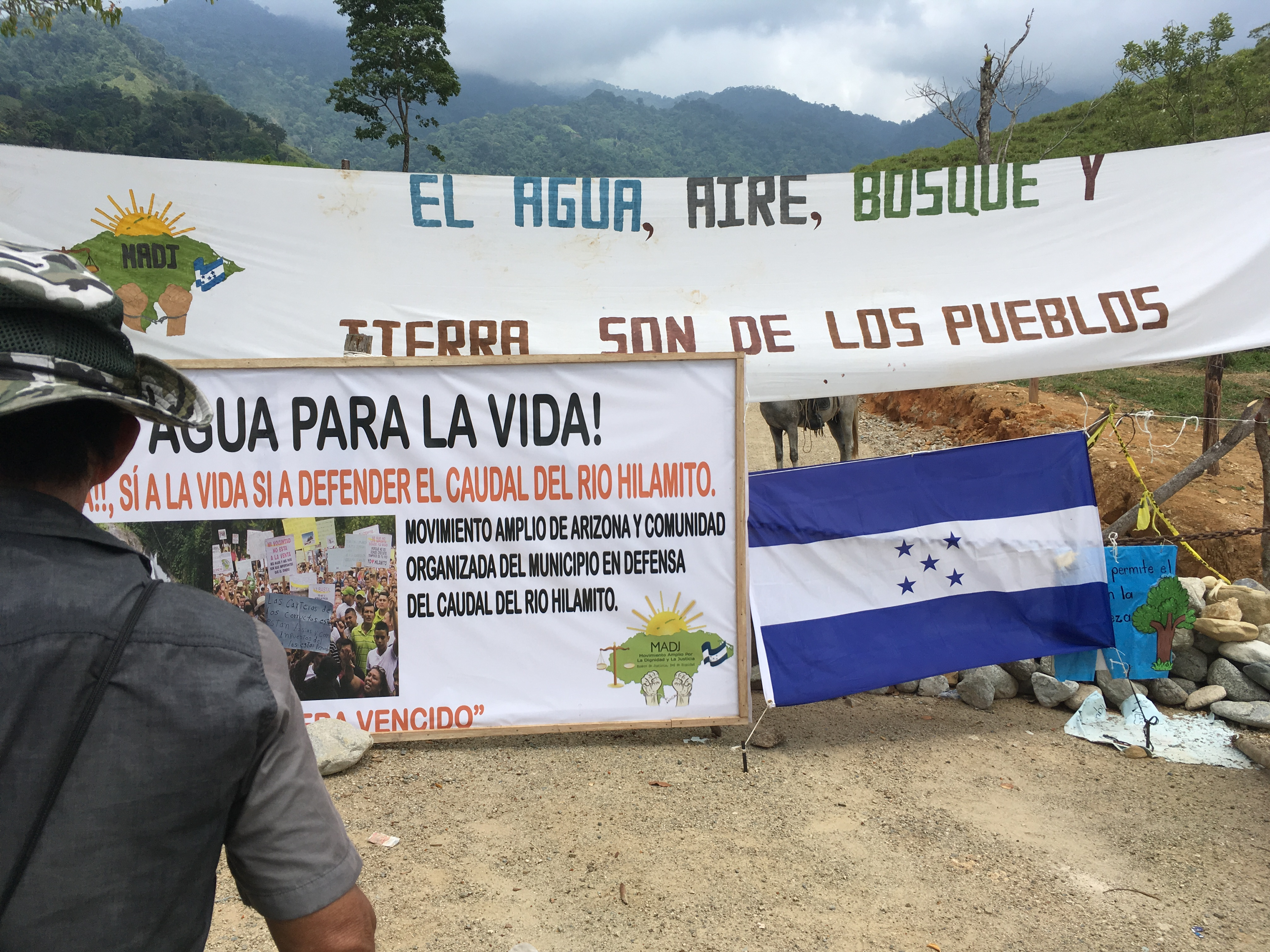 Picture is of a banner, sign, and Honduran flag that cover barbed wire and make up a barricade
