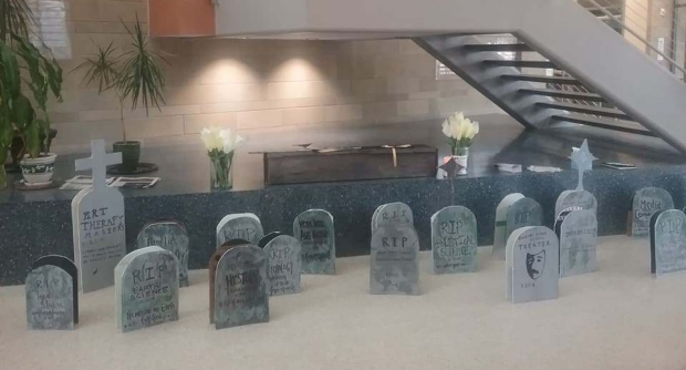 picture is of 25 handmade headstones with the names of academic programs set out in a univeristy building. in the background is a cardboard casket flanked by paper flowers.
