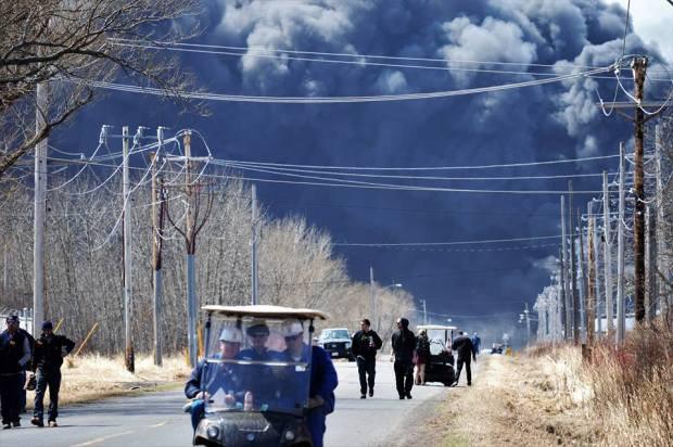 Photo shows black cloud of billowing smoke with workers walking away toward the camera, and many power lines.