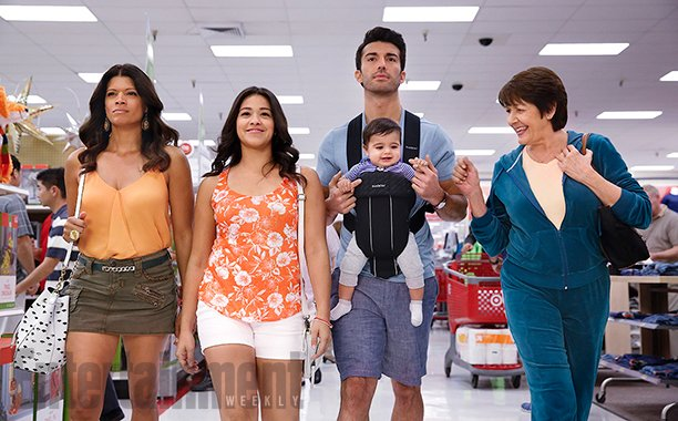 Photo with four characters from show walking in Target store: Xo looks determined, Jane is smiling, Rafael seems unhappy and has baby Mateo strapped to him, and Alba is smiling and playing with the baby.