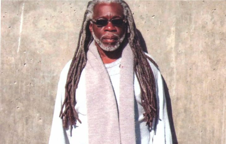 photograph of Dr. Mutulu Shakur in the sun against a concrete wall
