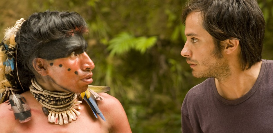 two men stare at each other. One man is in costume as an indigenous Taino man in the time of Columbus while the other wears a t-shirt.