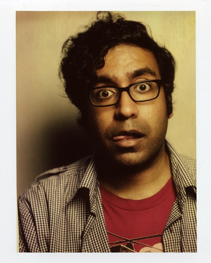 Picture of Hari Kondabolu head and shoulders with his tongue sticking out, eyes wide open to the camera
