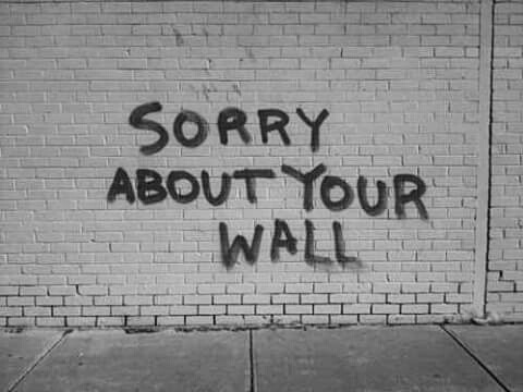 "a brick wall with a graffito that says just ""sorry about your wall"""