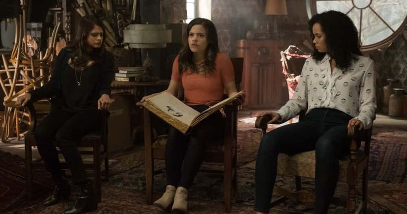 Picture of three women in an attic (the Vera sisters) looking at a large old book (the Book of Shadows).