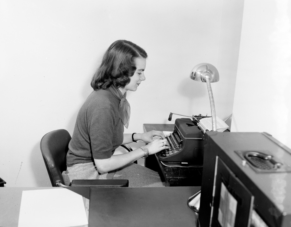 A young white woman sits at a typewriter in an office in France in the late 1940s. She is pictured from the side, with a desk and another box with a blurry red cross on it a bit blurry in the foreground as she types.